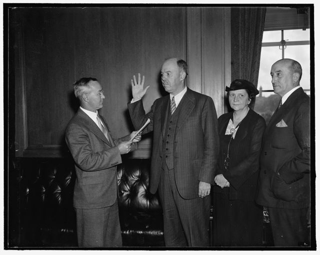 New U.S. Commissioner of immigration takes oath. Washington, D.C., Aug. 26. James L. Houghteling, newly appointed U.S. Commissioner of Immigration, today took the oath of office and assumed his duties. In the photograph, left to right: J.C. Watts, Assistant Chief Clerk of Labor Department, who administered the oath; James L. Houghteling; Secretary of Labor Frances Perkins; and Assistant Secretary of Labor Edward F. McGrady, 8/26/37