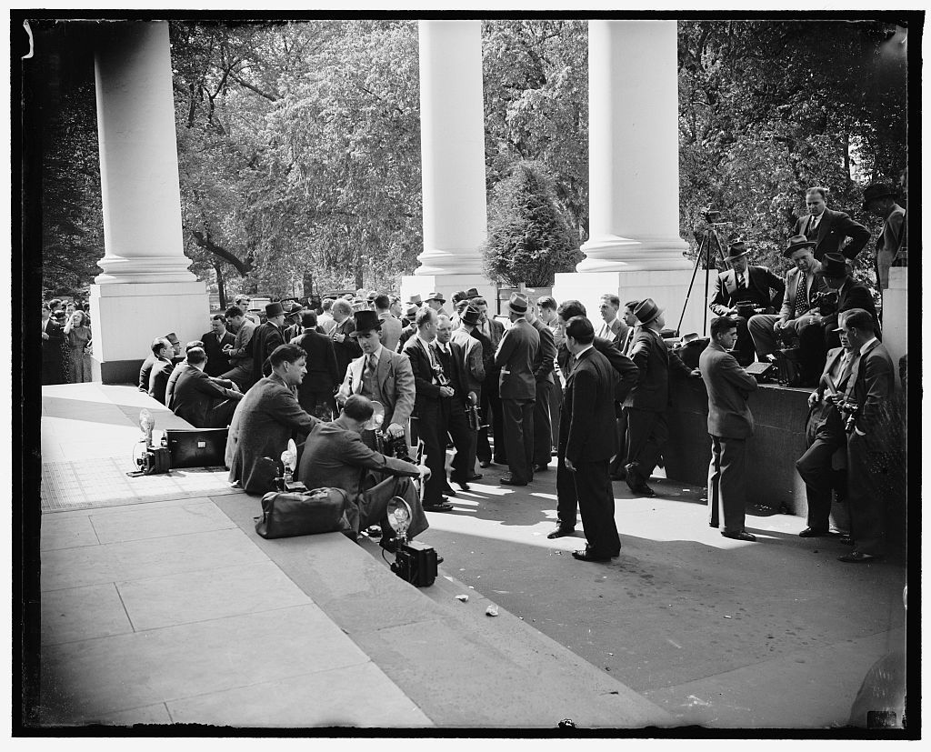 Newsmen await Henry Ford. Washington, D.C., April 27. Reporters and news cameramen waiting outside the White Housue for Henry Ford to emerge from a conference with President Roosevelt. The wait was in vain, as far as news was concerened, because the motor magnate refused to make a statement of leaving, 4/27/38