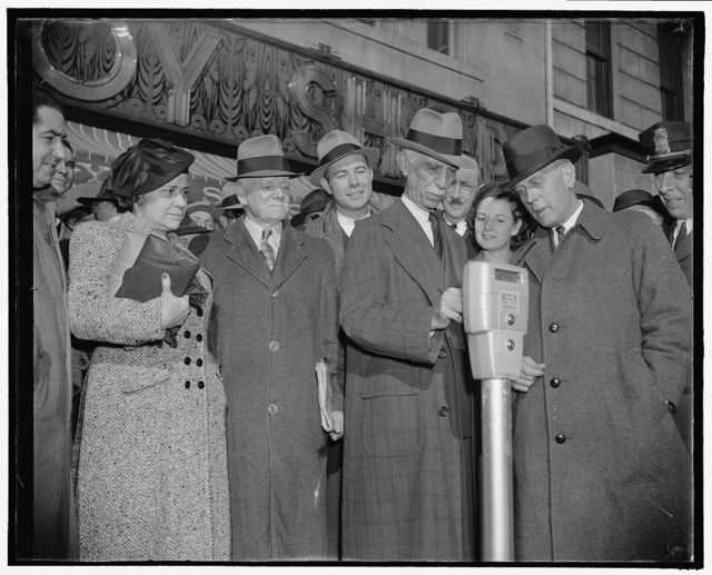 Parking meters for the Nation's Capitol. Washington, D.C., Nov. 14. Commissioner Melvin Hazen and William Van Duzer, putting the first nickel in the parking meters ordered by Congress for a test in Washington. Parking will be at the rate of five cents an hour, with no extensions for more nickels, 11/14/38
