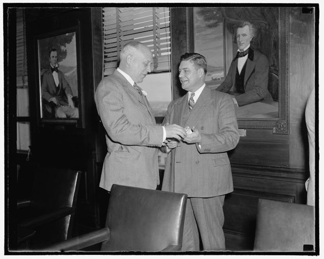 Perfect Harmony Washington, D.C., Nov. 7. Perfect harmony prevailed today as President Roosevelt's Special Committee of Rail Labor and Management representatives discussed proposed recommendations for legislative aid for the industry. Here we see George Harrison, right, President of the Brotherhood of Railroad Trainmen, as he accepts a cigarette from M.W. Clement, President of the Pennsylvania Railroad, 11/7/38