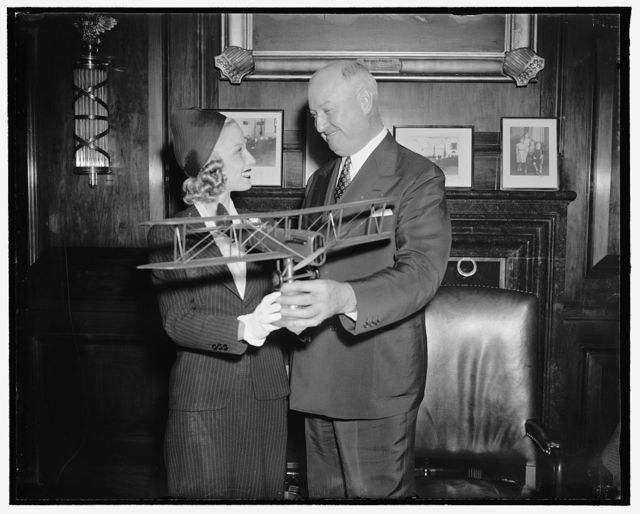 "PMG Farley receives airmail plane model. Washington, D.C., May 18. Postmaster General James A. Farley, receives from Miss Marion Weldon, Paramount Starlet who is playing in the Paramount production ""Men with Wings"" a model of the De Haviland Liberty plane used twenty years ago for carrying airmail, sent from Hollywood as a gift from William Wellman, producer-director of ""Men With Wings"" a history of air mail. Miss Weldon is also taking part in National Airmail week here in Washington, 5/18/38"
