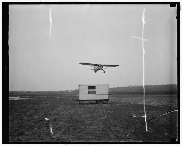 Portable trailer in use in blind landings. Washington D.C. This portable trailer where all the equipment is enclosed can be easily transported to any position on the Airdrome so that the pilot can approach the field into the wind for his landing. All the beam control is dispatched from this trailer to the instrument in the cockpit of the plane while at the same time the pilot is in contact with the airport control tower. Photo shows the plane in a test taking off over the trailer in a test at the Airdrome