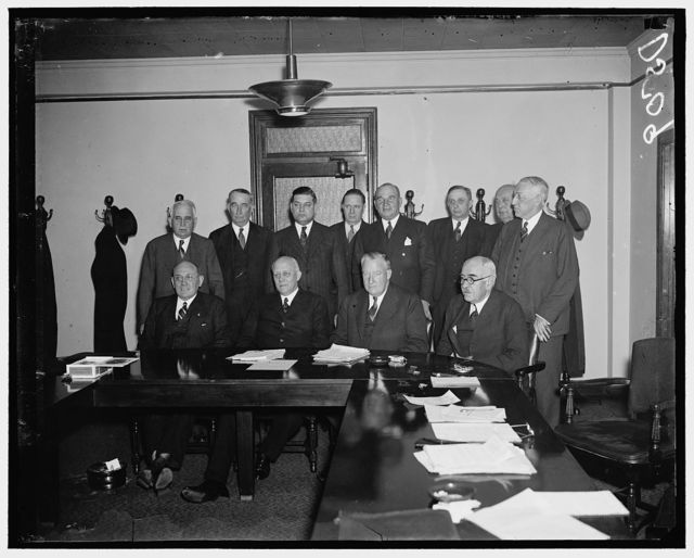 Railway Labor and Capital meet. Washington, D.C., Jan. 7. In compliance with a suggestion made by President Roosevelt in December, a joint conference between committees representing railway labor and railway managements was held here today. The most important matter considered was the Railroad Retirement Act situation, but no conclusion was reached. In the photograph, left to right: (seated) J.A. Phillips, Order of Railways Conductors; M.W. Clement, President of the Pennsylvania Railroad; and George B. Elliot, President of the Atlantic Coast Line; standing, left to right: E.J. Manion, Order of Railway Telegraphers: James J. Delaney, President, Masters, Mates, Pilots of America; George M. Harrison, Chairman of The Railway Executives Association of Railroads; J.B. Hill, President, Nashville, and Executive Officer, Missouri Lines; H.A. Scandrettm Trustee of the Chicago, Milwaukee, St. Paul and Pacific