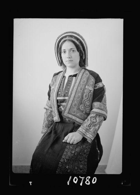 Ramallah type (Wedad Khuri). Weddad in finely embroidered Ramallah costume, seated, 3/4 figure