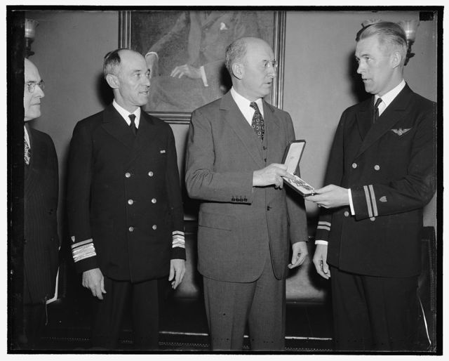 Rewarded for courage. Washington, D.C., May 12. Lieut. C.B. Olson (right) United States Coast Guard, receiving from Secretary of the Treasury Morgenthau today the distinguished Flying Cross, The first to be awarded to a Coast Guard Aviator. Lieut. Olson was awarded the cross in recognition of a flight in storm and darkness he made 300 miles to sea from the Miami, Fla. air station to n army transport and returning safely with an army officer in desperate need of an operation. The flight was made in June 1935. On the left is Rear Admiral R.R. Waesche, Commandant of the Coast Gaurd, 5/12/38