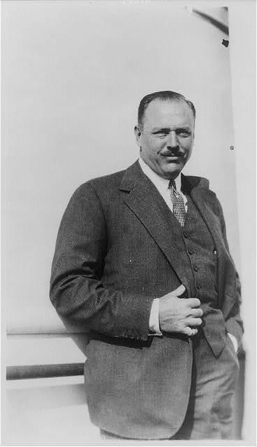 [Robert Low Bacon, 1884-1938, three-quarter length portrait, standing, facing right]