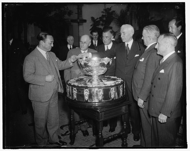 Secretary of State presides at Davis Cup drawing. Washington, D.C., Feb. 3. Presiding at the Davis Cup drawing at the Pan American Union today, Secretary of State Cordell Hull pulls Japan's pairing out of historic bowl first and hands it over to Yakichiro Suma, Counselor of the Japanese Embassy. In the photograph, left to right: Yakichiro; Russell B. Kingman, Treasurer of the United States Lawn Tennis Association; Joseph Ward, First Vice President; Secretary Hull; Holcomb Ward, President of the USLTA; and Wallis Pate, Capt. of this year's Davis Cup team, 2/3/38