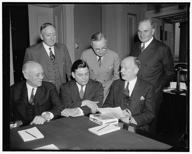 Senator Wheeler discusses rail road legislation with rail leaders. Washington, D.C., April 21. At a special meeting at the Capitol today, Senator Wheeler, Democrat of Montana, Chairman of the Senate Interstate Commerce Committee, discussed with representatives of Railroad Labor and Management the possibilities for railroad legislation at this session of Congress. In the photograph, left to right: (seated) Martin W. Clement, President, Penna Railroad; George M. Harrison, representing the Labor Executives Association; and Chairman Wheeler. In the back row, left to right: Ralph Budd, President, Chicago, Burlington, and Quincy R.R., Senator Harry S. Truman, member of the Interstate Commerce Committee, and J.J. Kelley, President of the Association of American Railroads, 4/21/38
