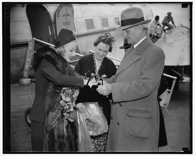 "Senatorial Aid. Washington, D.C., May 15. Senator William Gibbs McAdoo, of California, comes to the aid of Miss Marion Weldon, Paramount starlet, as she searches for her beauty aids before greeting the throng on her arrival at Washington Airport today. Miss Jean O'Connell, daughter of Ambrose O'Connell, Executive Assistant to the Postmaster General, is pictured in the center. Miss weldon is here to participate in National Airmail Week as a representative of Hollywood, and honor for which she was selected by the 22 pilots and stunt men who are appearing in with her in the forthcoming Paramount technicolor production ""Men with Wings,"" 5/15/38"
