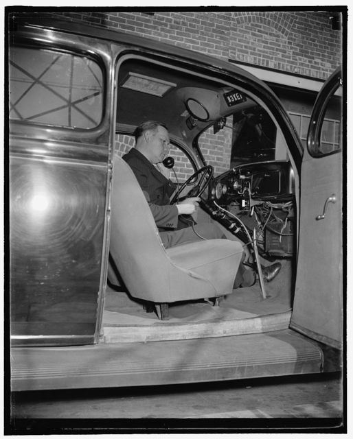 Sergeant Frank M. Beall, in charge of the station, seated in the experimental 2-way communication car. He is removing the telephone transmitter to make a call, 10/38