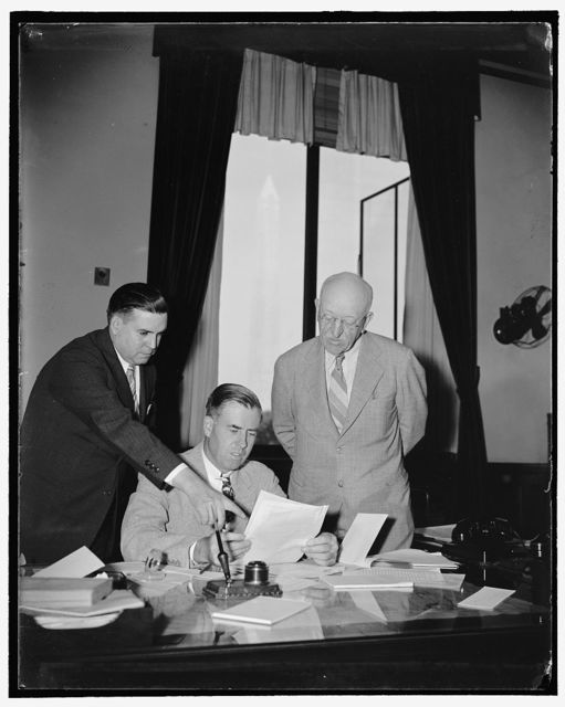 Signing New York milk marketing order Washington, D.C., Aug. 26. Sec. of Agriculture Henry Wallace Center; Commissioner Holton V. Noyes, right; of the New York Department of Agriculture, and F.R. Wilcox, director of the AAA division of marketing and marketing agreements, are looking over the Federal Milk Marketing order for the New York metropolitan marketing area. This order, which was approved by more that 70 percent of dairymen supplying the New York City market with milk in a referendum held recently throughout the New York milkshed, establishes uniform minimum prices to be paid dairymen handlers. The marketing agreement program affects about 10 million people who get an average daily supply of about 6 and a half million quarts of milk from the New York milkshed, 8/26/38
