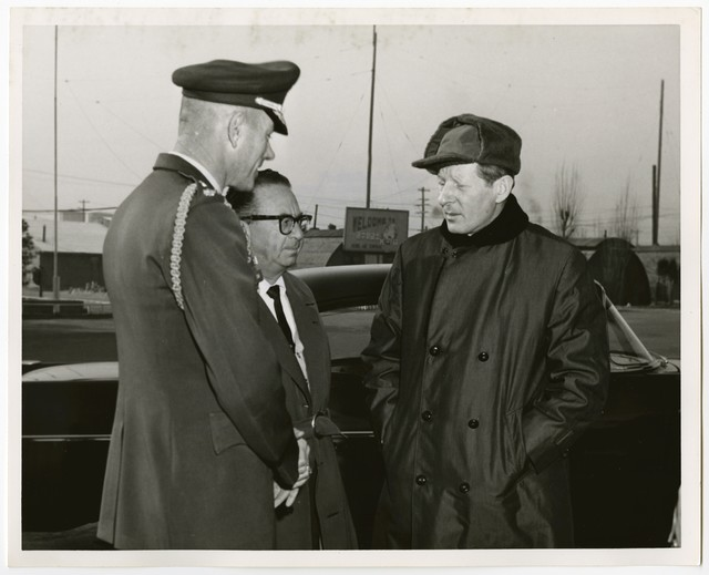 Singer, Comedian Danny Kaye strikes a serious pose before his departure from ROK's K-16 Airport as he chats with his pianist, accompanist Sammy Prager and escort, Maj Sidney H Cook, Jr.