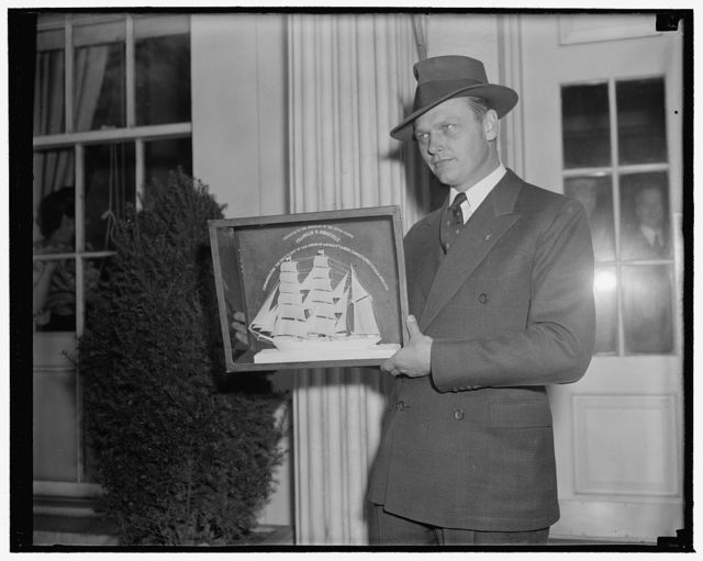 Skipper of Yankee Clipper presents president with model of old Portuguese sailing bark. Washington, D.C., April 20. Capt. Harold Gray, who recently piloted the Yankee Clipper over the Atlantic for the first time, today presented President Roosevelt with this model of an old Portuguese sailing bark. It was carved from memory by Padre Joso Pereira de Silva, who is seventy-five years old