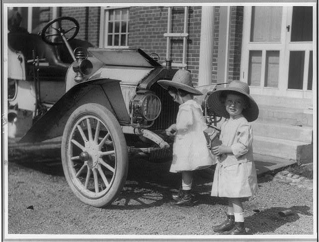 [Small twin girls in front of 1911 Buick roadster]