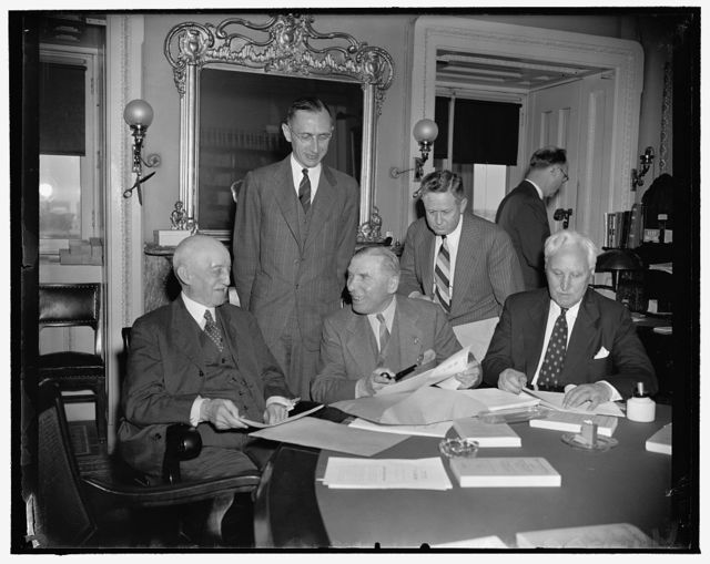 State Department confers privately with House on amendments to Neutrality Act. Washington, D.C., June 5. Meeting today in executive session, the House Foreign Affairs Committee conferred with officials from the State Department on proposed amendments to the present neutrality laws. Left to right, seated: R. Walton Moore, State Department counselor, Chairman Sol Bloom, Green H. Hackworth, State Dept. legal advisor; standing: Carlton Savage, assistant to Moore, and Rep. Charles A. Eaton of N.J.