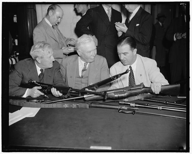 Study Johnson semi-automatic rifle. Washington, D.C., May 29. Senator Morris Sheppard, left, Chairman of the Senate Military Affairs Committee, Maj. Gen. George A. Lynch, U.S. Chief of Infantry, and Senator A.B. Chandler of Kentucky, inspect the Johnson semi-automatic rifle which may replace the Garand gas-operated rifle as the Army's standard shoulder weapon. Capt. Melvin M. Johnson, inventor of the Johnson rifle, told the Senate Military Affairs today when it began consideration of a bill to change the Army's standard shoulder weapon, that his rifle could be manufactured more rapidly than the Garand