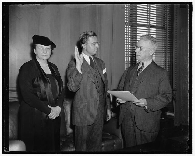 Sworn in as administrator of Public Contracts Division of Department of Labor. Washington D.C. L. Metcalfe Walling was today sworn in as Administrator of the Public Contracts Division of the Department of Labor which is enforcing the provisions of the Walsh-Healy Act. Walling has been Director of the State Labor Department of Rhode Island for two years. In the photograph, left to right: Secretary Perkins, L. Metcalfe Walling, and Samuel M. Gompers, Chief Clerk of the Departement of Labor administering the oath