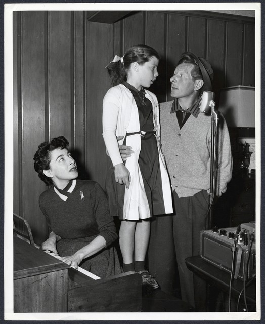 [ Sylvia (at piano), Dena and Danny in front of microphone, possibly recording]