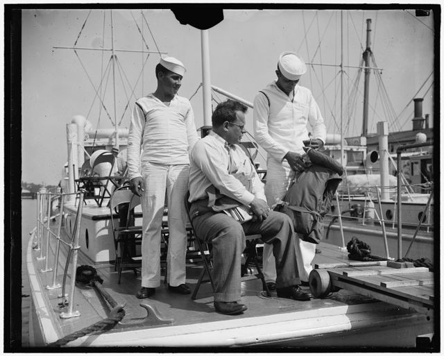 Texas Solon leaves for Roosevelt's pow-wow. Annapolis, MD. June 25. Rep. Maury Maverick, of Texas was the first to board the boat for Jefferson Island today enroute to attend the President's party and confab for Democratic members of Congress. The diminutive Texan is shown being instructed in the use of the life preserver by two Bluejackets. 6/25/37