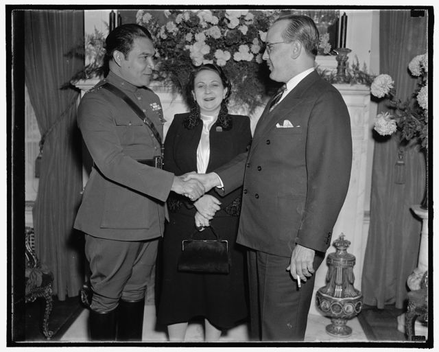 The Cuban Dictator and the Mrs. Washington, D.C., Nov. 10. Col. Fulgencio Batista, the Cuban Army Sergeant who rose to the Dictatorship of Cuba, arrived in Washington today for a round of military reviews and dinners of state which will screen some fine international conversations, the visit has a high flavor of mystery, the War Department has been at elaborate pains to stick to its story that the Colonel, who never set foot outside of Cuba until two days ago, is suddenly traveling at the age of thirty seven years, he is shown with his seldom photographed wife, and the ambassador from Cuba Dr. Pedro Fraga[?], at the Cuban Embassy, 11/10/38
