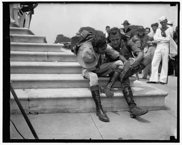 Walk 800 miles to attend Boy Scout Jamboree. Washington, D.C. June 16. Two Venezuelan Boy Scouts, Rafael Petit, left and Juan Carmona, right, examining their boots after tramping 25 miles a day for two years in order to attend the Boy Scout Jamboree in Washington the left Caraca, Januray 11, 1935 arriving in Washington today.
