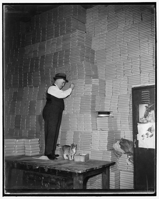 Watchdog of senate folding room has 'crop control' of own. Washington, D.C., Dec. 3. Since 1900 John W. 'Happy' Deards has been foreman of the Senate folding room which carries with it the responsibility of guarding thousands of volumes of Senate records including congressional records, agriculture yearbooks, senatorial eulogies, I.C.C. reports and books on horses and cattle. He is now wrestling with the problem of finding space for the harvest of 1938 agricultural yearbooks--35,000 volumes--shown under his feet and all around him. Deards says the books on horses and cattle which the government published in 1892 are still the most in demand of any others in the huge collection