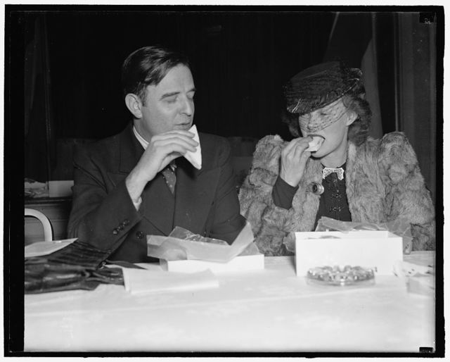 Wife of Supreme Court justice enjoys box at benefit for Spanish relief. Washington, D.C., March 13. Persons in all walks of life turned out last night at the National Press Club for the combination auction and box supper given for the benefit of the Spanish Relief Campaign. In this picture, Mrs. William O. Douglas, wife of the Supreme Court Justice, seemed to enjoy her dinner from a box as she listened to Leon Henderson, member of the S.E.C., preside as auctioneer, 3-13-40