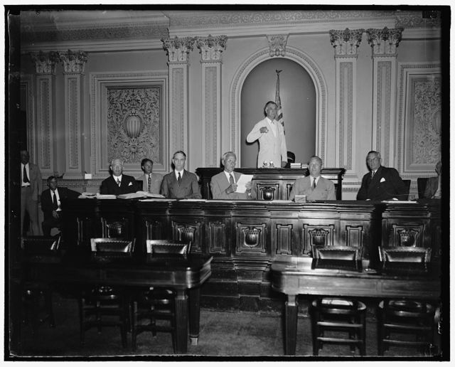 Will run senate machine while Vice President Garner is absent. Washington, D.C. June 14. While Vice President Garner is vacationing in Texas during the next few weeks, Senator Key Pittman, President Pro Tem will preside over the Senate. Senator Pittman is shown with other officers of the Senate as the session opened this morning. Left to right: Chesley W. Jurney, Sergeant at Arms; Leslie L. Biffle, Secretary to the Majority; Charles L. Watkins, Parliamentarian and Journal Clerk; John C. Crockett, Cheif Clerk; Senator Key Pittman; Emery L. Frazier, Legislative Clerk; and Col. Edwin A. Halsey, Secretary. 6/14/37