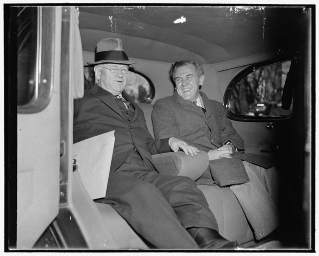 WPA Administrator and ace 'brain truster.' Washington, D.C., Dec. 6. Secretary of Interior Harold Ickes and 'Tommy' Corcoran, the administration's ace - brain truster, pictured leaving the White House today after a conference with President Roosevelt