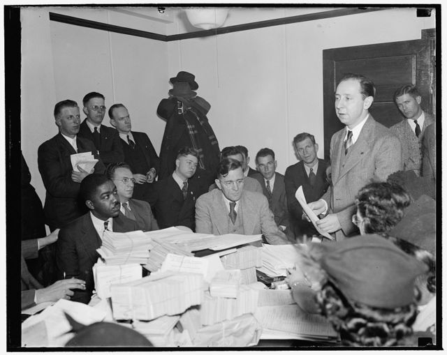 WPA workers protest relief cuts. Washington, D.C., Dec. 15. WPA workers from 26 states, head by David Lasser, President of the Workers Alliance, today protested to Assistant Administrator Aubrey Williams the recent cuts in relief. Their kicks were against the current wage scales, geographical wage differentials, inadequate number of WPA enrollees and the 'unjust and unfair' labor relations setup. Lasser is on the right and Aubrey Williams in center seated, 12/15/38