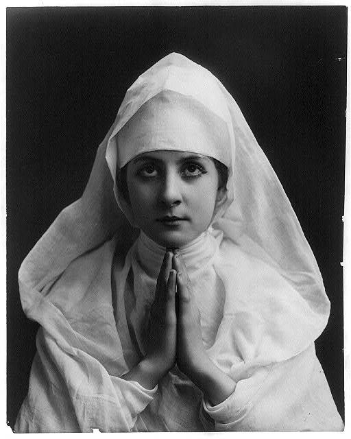 [Young woman modeling: Half lgth., wearing nun's white habit and praying]