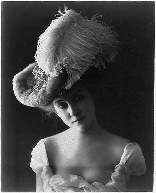 [Young woman modeling: head and shoulders, wearing plumed hat and low-cut dress]
