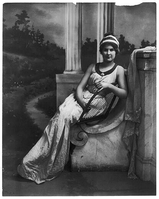 [Young women modeling: Full lgth., seated, holding lyre]
