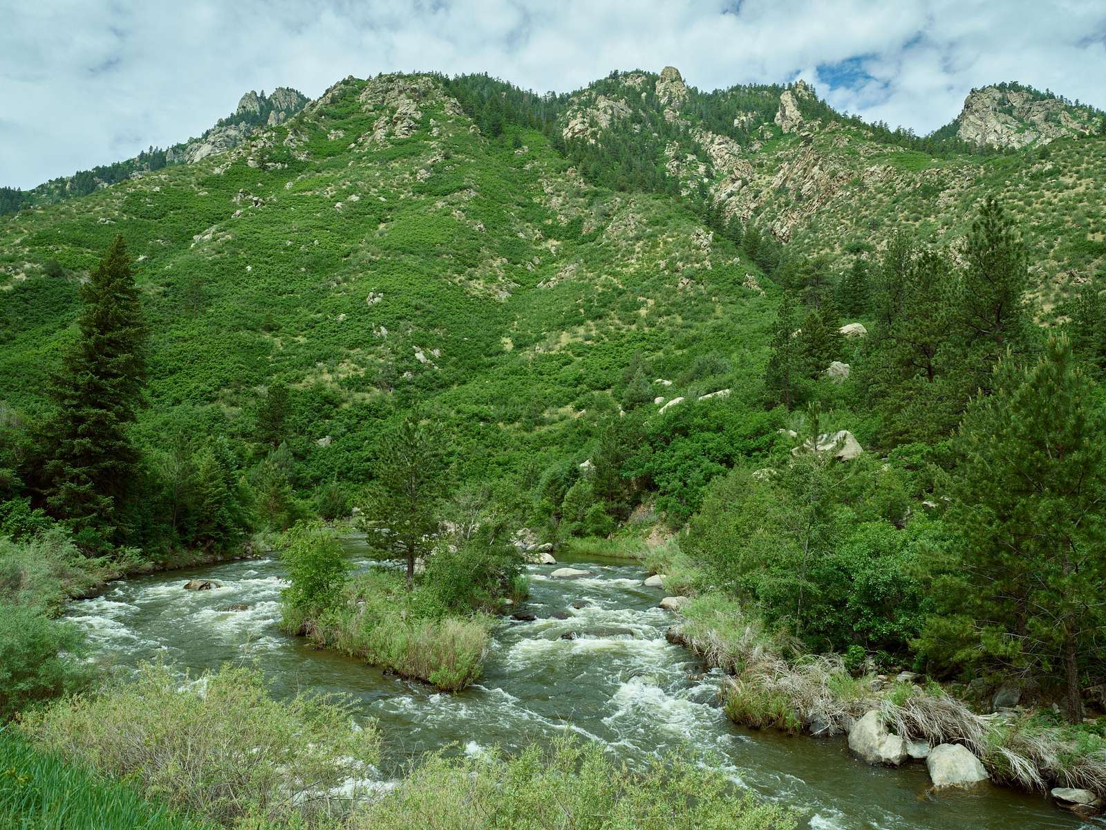 View of the rushing South Platte River in Waterton Canyon in Jefferson County, Colorado, one of metropolitan Denver's favorite workout venues, where bicylists, hikers, walkers, and horseback riders exercise in a beautiful, invigorating, patrolled environment managed by Denver Water, the city's public water utility, and the U.S. Forest Service