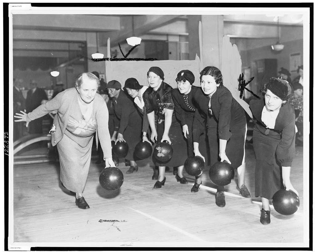 [Floretta McCutcheon demonstrates the proper way to hold a bowling ball as eager students look on] / World Telegram & Sun photo.