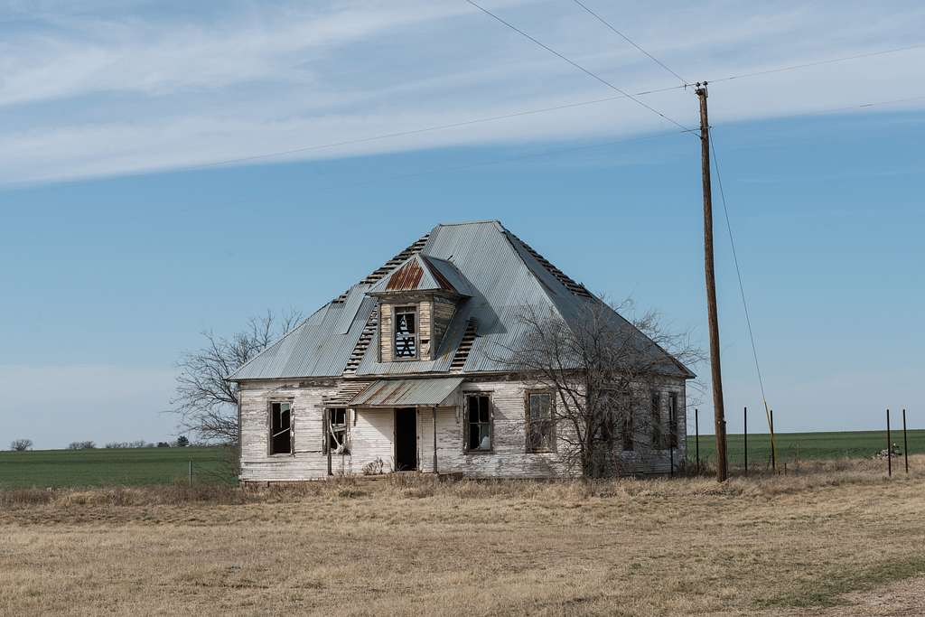 An old home with a steep pitched roof, frequently seen in Texas, has seen better days in the countryside around the town of Ballinger in Runnels County, Texas
