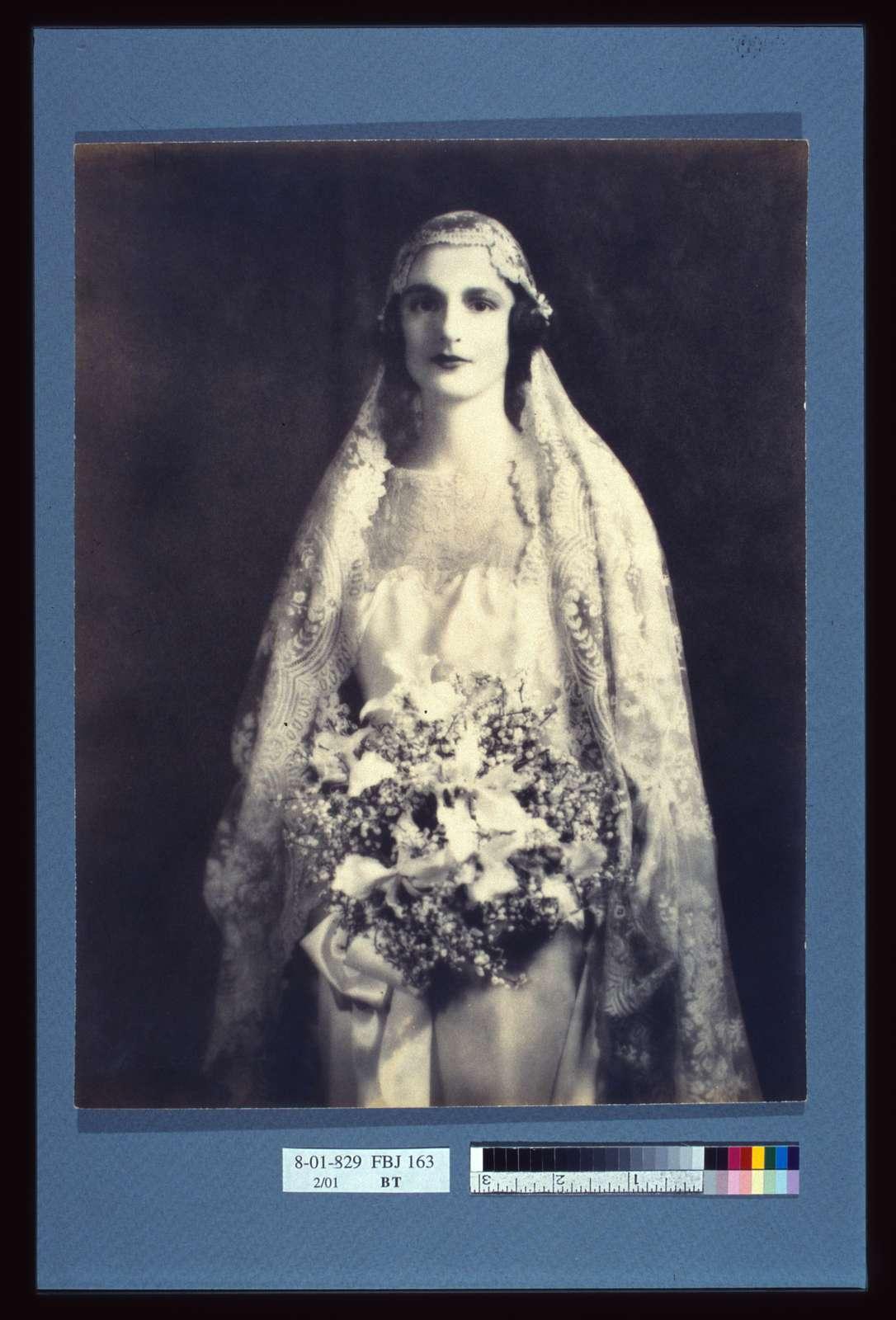 [Bride holding a wedding bouquet, facing front, three-quarter length portrait]