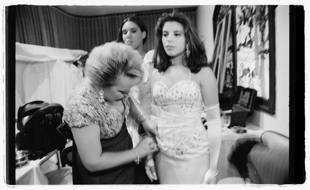 Elsa Mantilla, backstage, helping beauty pageant contestants with their gowns.  Many of the gowns were made in Elsa's dress shop.
