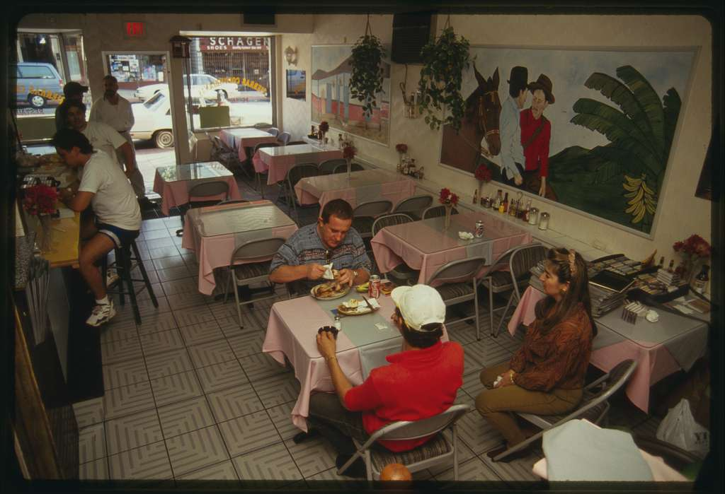 Interior of restaurant with customers sitting at tables; murals on the wall depict scenes from Colombia.
