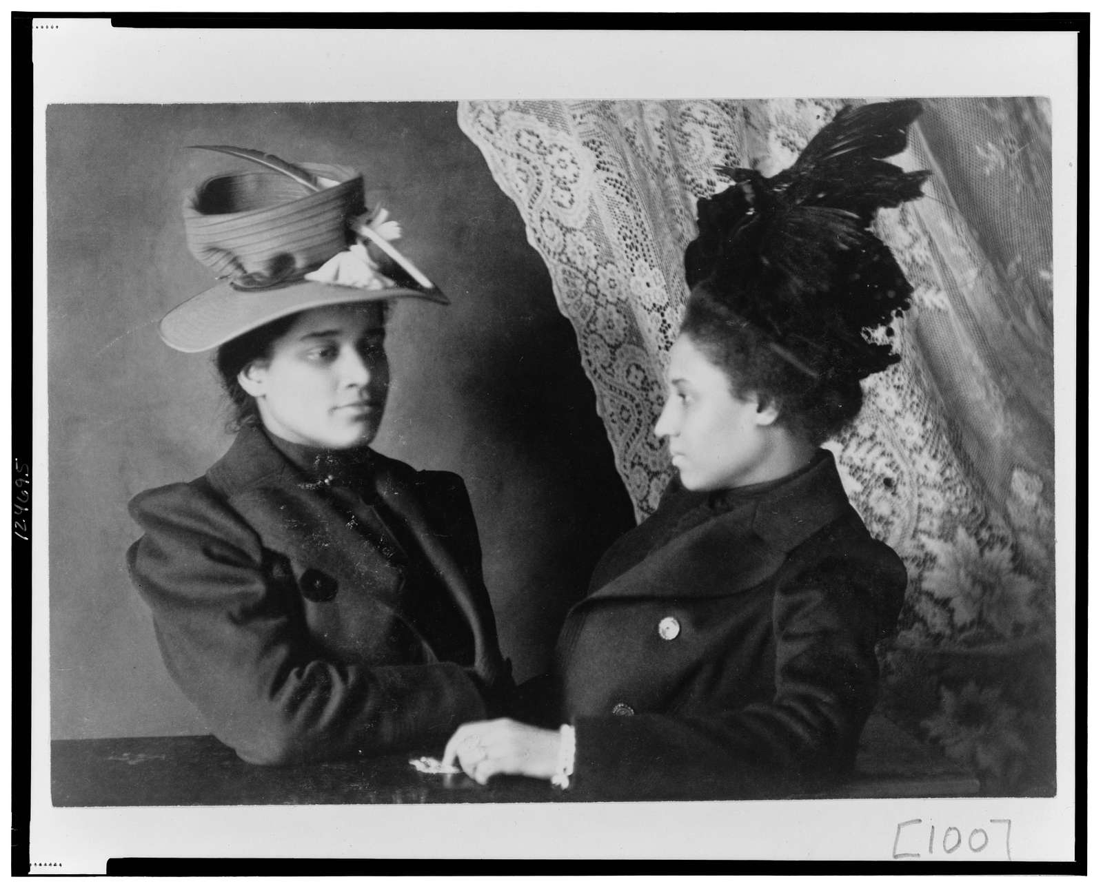 [Two African American women, half-length portrait, facing each other]