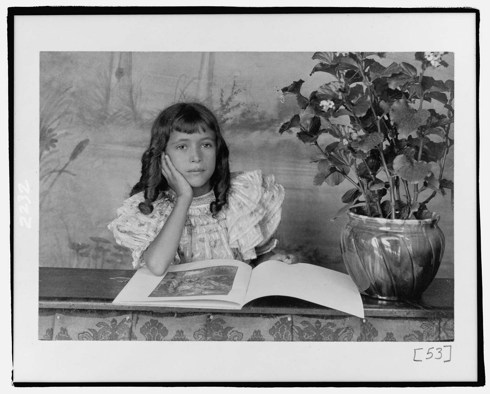[Daughter of Thomas E. Askew, head-and-shoulders portrait, seated, right hand on cheek, with open book]