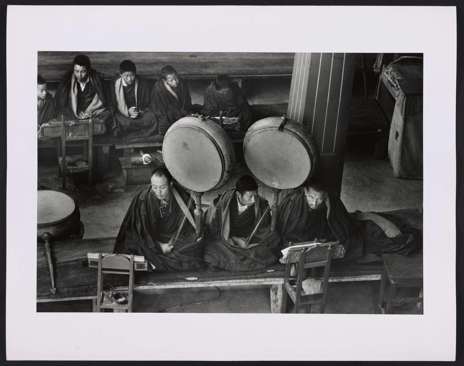 [Drumbeats accompany prayers inside temple]