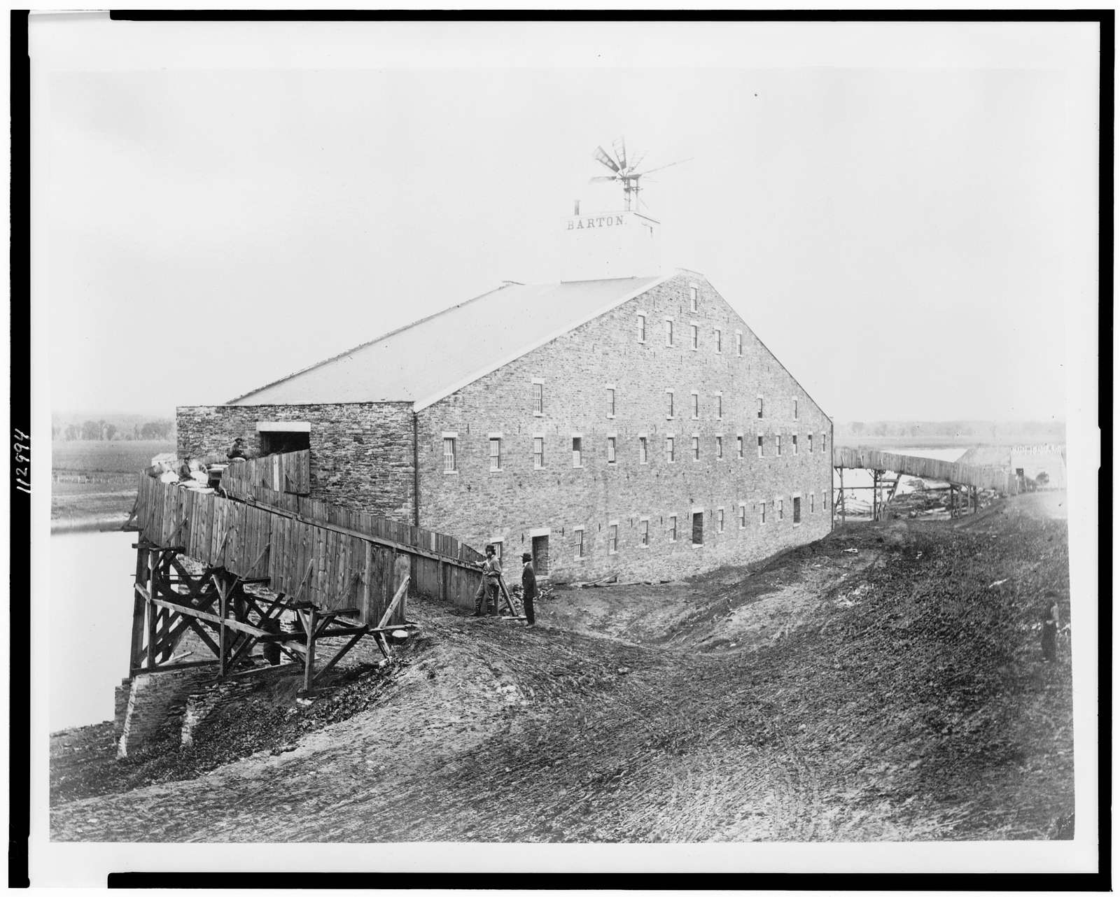 """[Lumber(?) mill with """"Barton"""" sign on top]"""