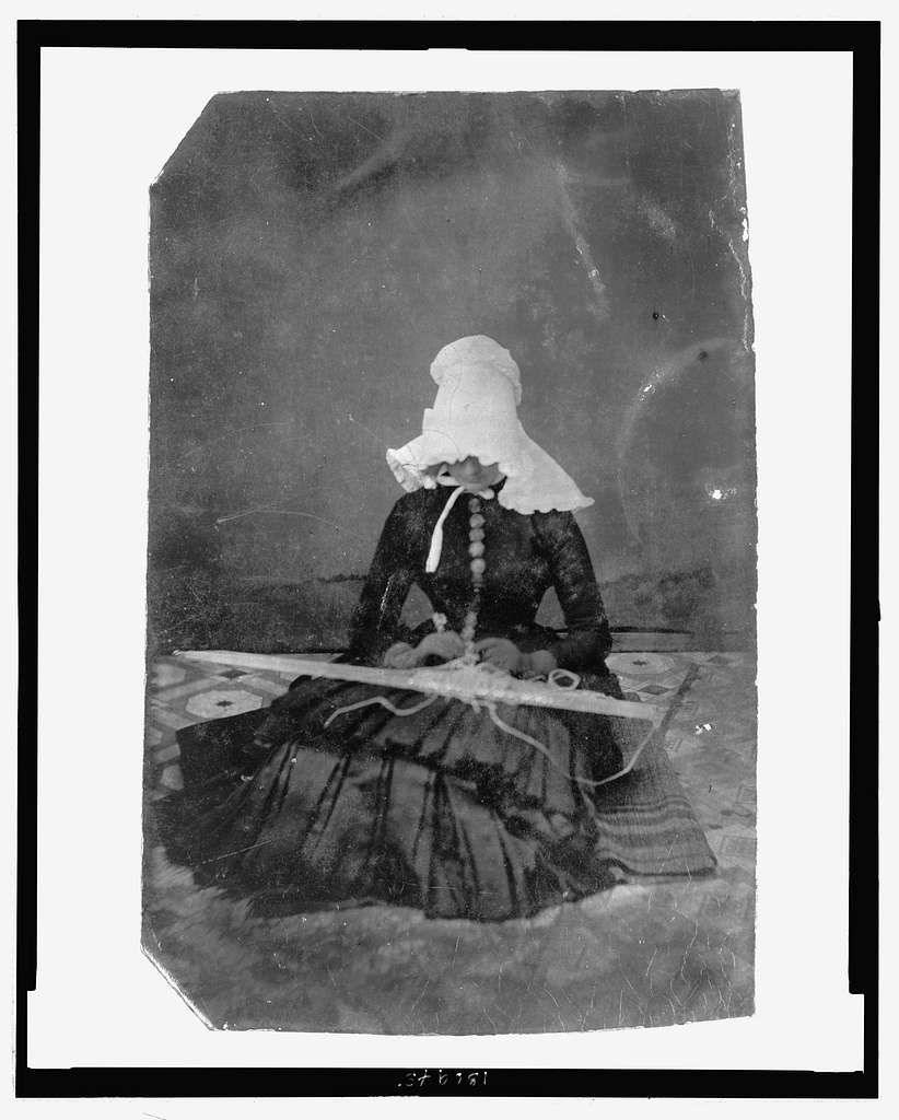 [Full-length portrait of a woman wearing a large ruffled bonnet, sitting on the floor while tatting(?)]