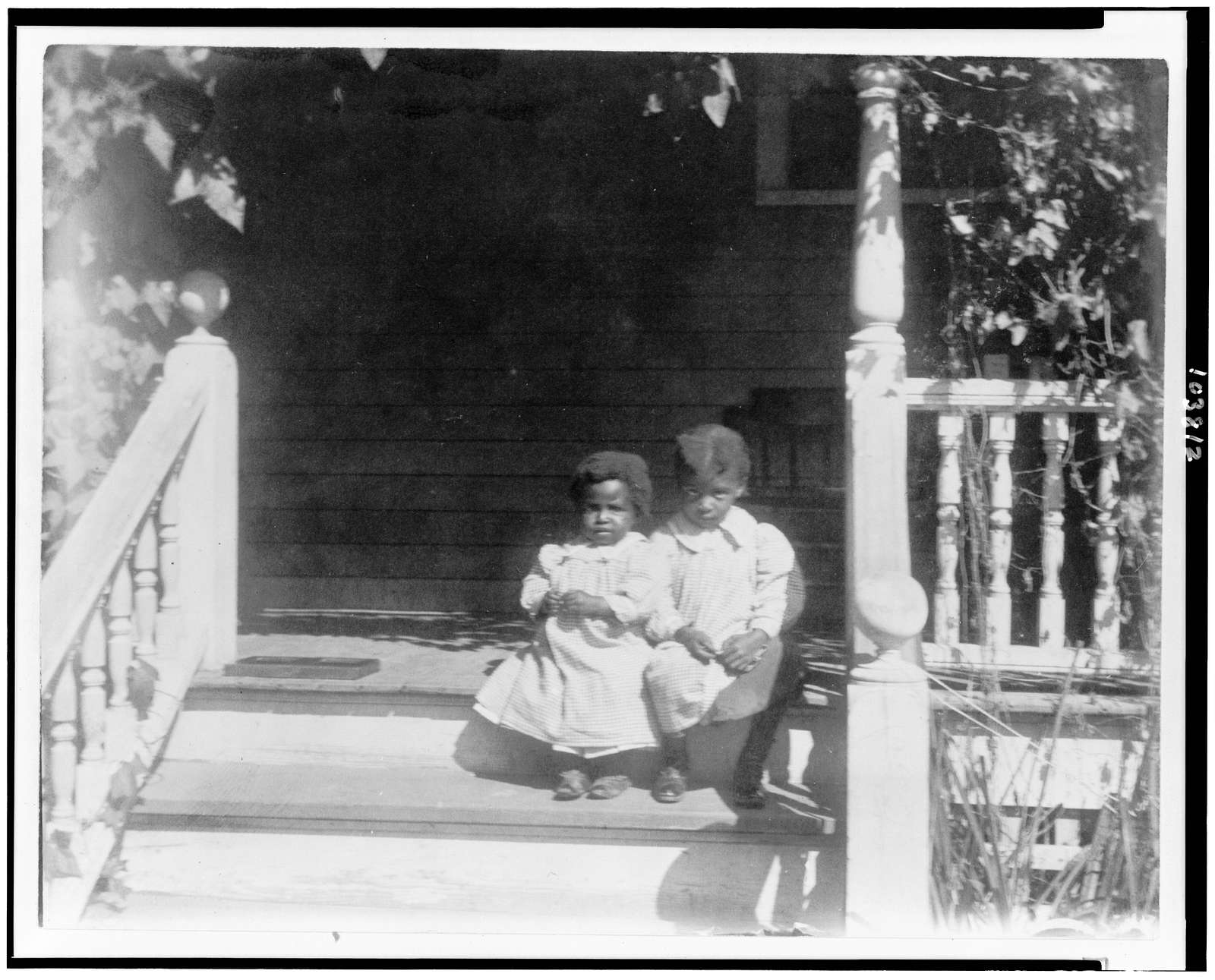 [Two African American children sitting on steps to porch]