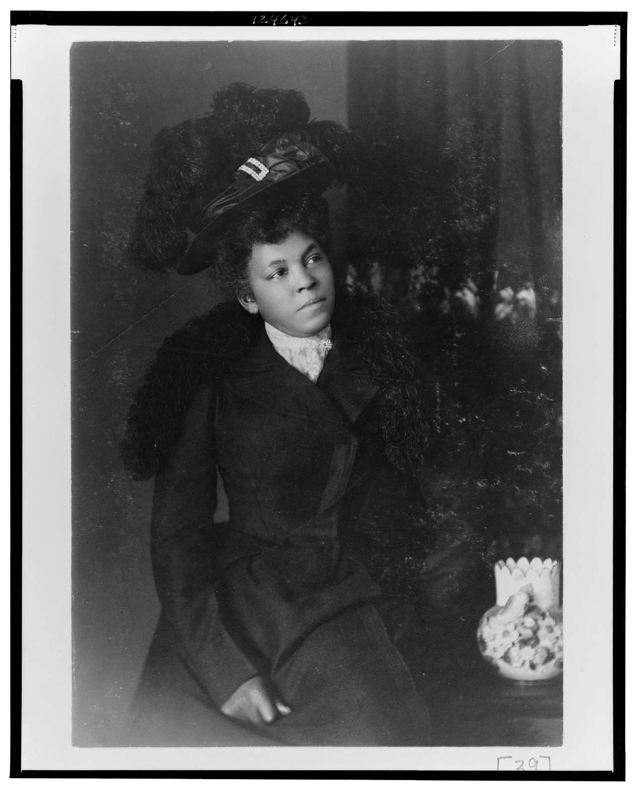 [African American woman, three-quarter length portrait, facing slightly right, wearing hat]