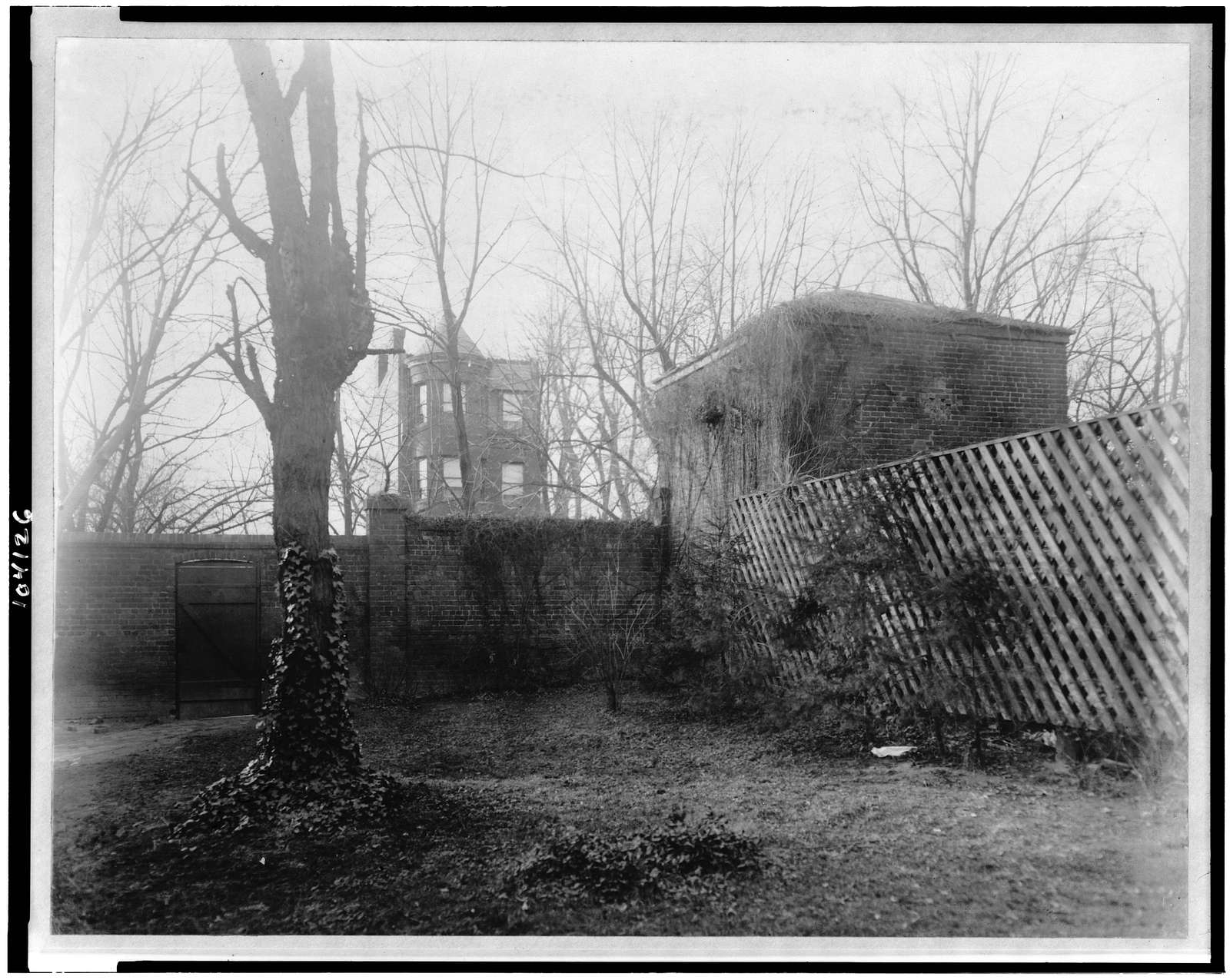 [View of stable at the Octagon House, Washington, D.C. with brick fence, trellis fence, and tree]