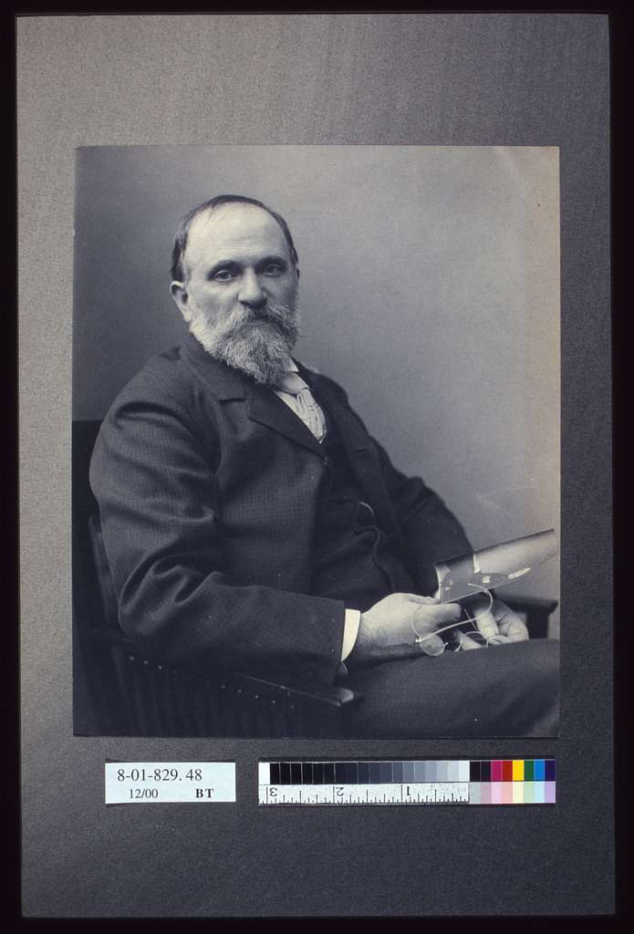 [Thomas Hovenden, artist, seated, holding a photograph(?), facing front, half-length portrait]