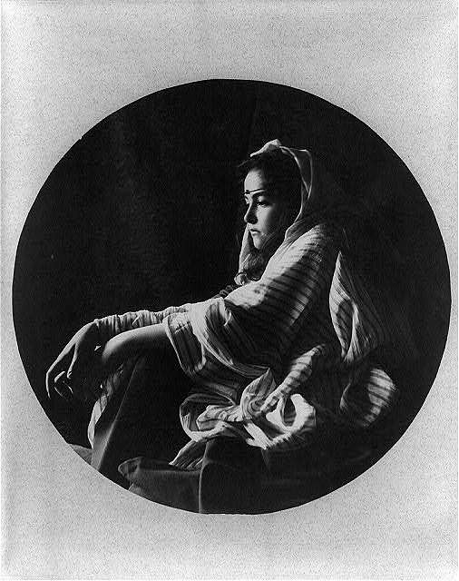 [Young woman in Middle Eastern costume and jeweled headband, seated on floor]
