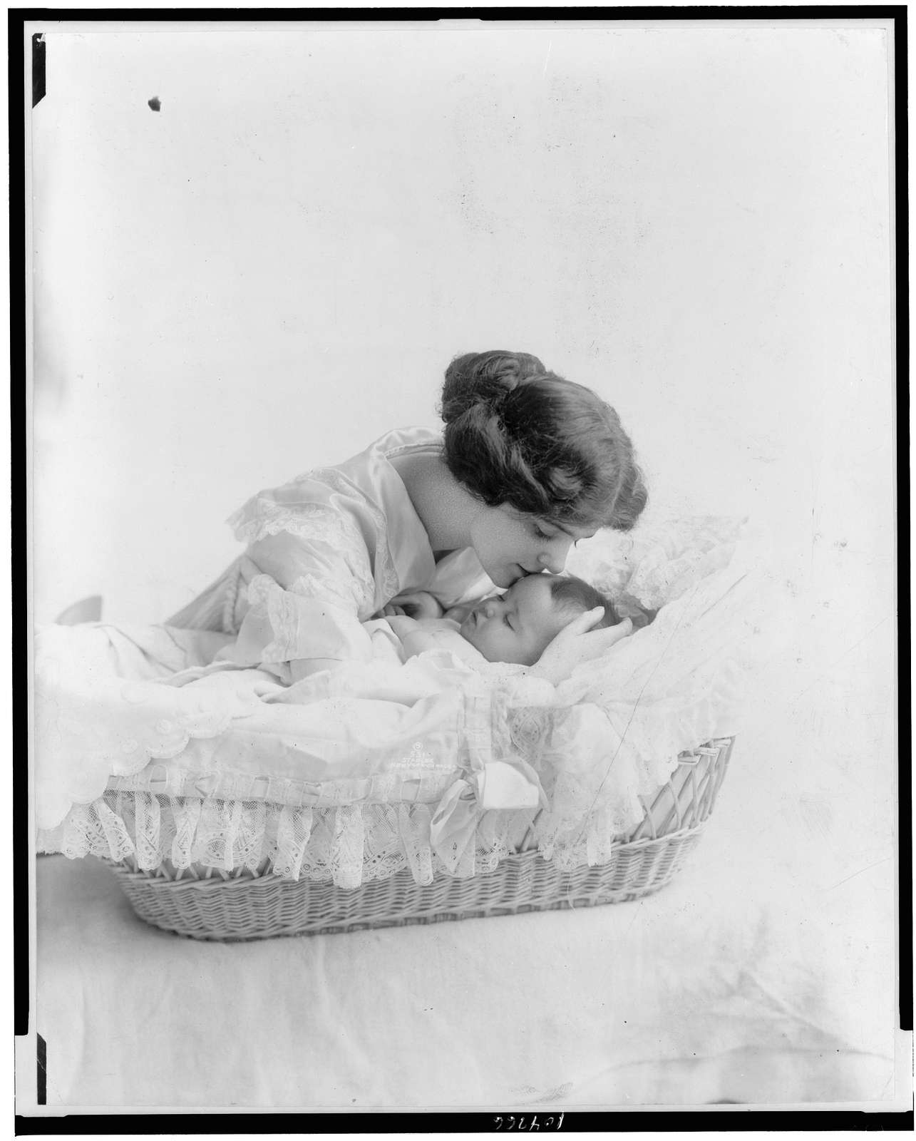 [Young woman kissing baby in bassinet]
